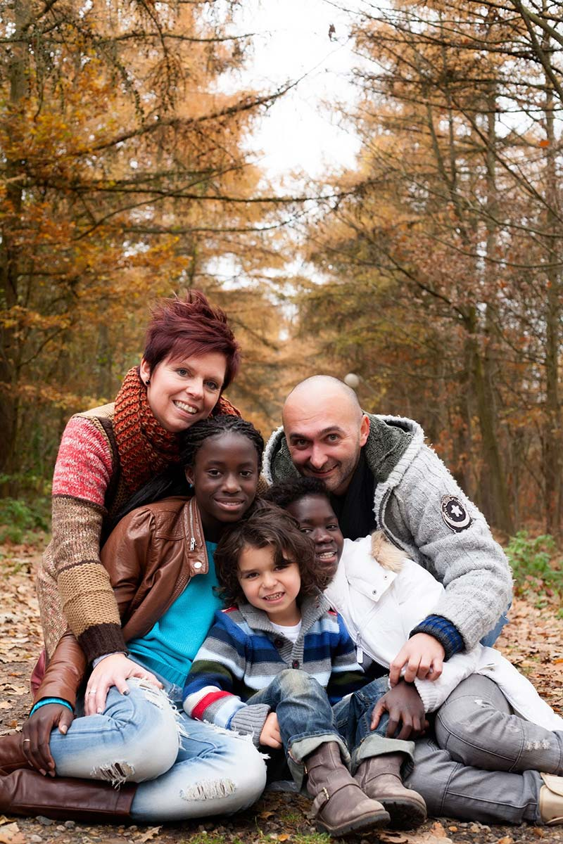 Portrait of a happy, mixed-race family posing in the woods in Autumn.